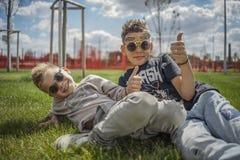 Chiuda su dei ragazzi che si siedono nel parco sull'erba verde Concetto 'nucleo familiare' felice fotografia stock libera da diritti