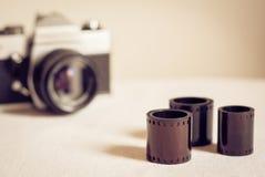Chiuda su dei rotoli di film con la retro macchina fotografica della foto Fotografie Stock