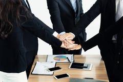 Chiuda su dei soci commerciali che fanno il mucchio delle mani alla riunione B Fotografia Stock Libera da Diritti