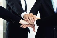 Chiuda su dei soci commerciali che fanno il mucchio delle mani alla riunione B Immagini Stock