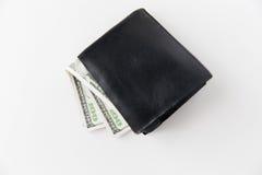 Chiuda su dei soldi del dollaro in portafoglio nero sulla tavola Fotografia Stock