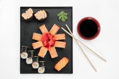 Chiuda su dei sushi del sashimi messi con i bastoncini e la soia su un vassoio servente fotografie stock libere da diritti