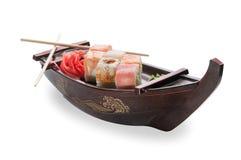 Chiuda su dei sushi del sashimi messi con i bastoncini e la soia su un vassoio servente della barca fotografia stock libera da diritti