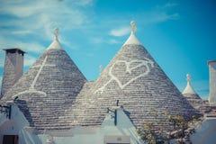 Chiuda su dei tetti conici delle case di un Trulli con i simboli dipinti Immagini Stock