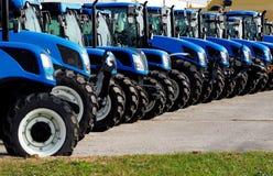 Chiuda su dei trattori nuovissimi in una fila Immagine Stock