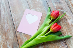 Chiuda su dei tulipani e della cartolina d'auguri con cuore Fotografie Stock Libere da Diritti