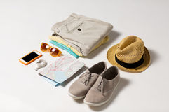 Chiuda su dei vestiti dell'estate e della mappa di viaggio sulla tavola Immagine Stock