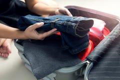 Chiuda su dei vestiti dell'imballaggio della donna di affari nella borsa di viaggio immagini stock