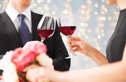 Chiuda su dei vetri tintinnanti del vino rosso delle coppie fotografia stock