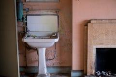 Chiuda su del bacino di mano e dello scaldabagno ossidato nel 1930 nello stile di deco di s sviluppato casa abbandonata, l'erpice immagine stock