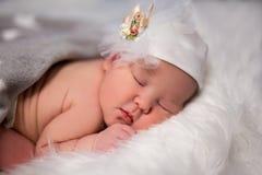 Chiuda su del bambino addormentato sveglio in cappello sopra bianco Fotografia Stock Libera da Diritti