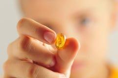 Chiuda su del bambino che tiene la pillola gialla Fotografie Stock