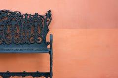 Chiuda su del banco d'acciaio contro una parete arancio Immagini Stock Libere da Diritti