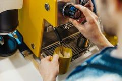 Chiuda su del barista che cuoce a vapore il latte nel lanciatore con la macchina del caffè fotografie stock libere da diritti
