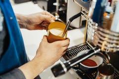 Chiuda su del barista che cuoce a vapore il latte nel lanciatore con la macchina del caffè immagini stock
