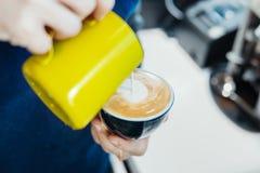 Chiuda su del barista che versa il latte cotto a vapore nella tazza di caffè che fa l'arte del latte immagine stock