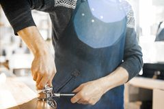 Chiuda su del barista con il compressore e pistone o portafilter che produce il caffè espresso fotografia stock