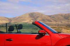 Chiuda su del cabriolet rosso nel paesaggio asciutto del deserto con il fondo delle montagne - Lanzarote, il EL Cotillo fotografia stock libera da diritti