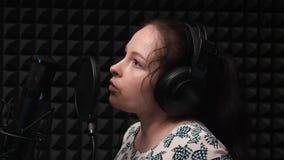 Chiuda su del canto sveglio castana della ragazza e delle canzoni di registrazione nello studio di musica vocale Processo di regi video d archivio