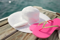 Chiuda su del cappello, della protezione solare e delle pantofole alla spiaggia Fotografia Stock