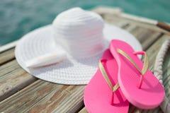 Chiuda su del cappello, della protezione solare e delle pantofole alla spiaggia Immagini Stock Libere da Diritti