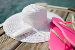 Chiuda su del cappello, della protezione solare e delle pantofole alla spiaggia Immagine Stock Libera da Diritti
