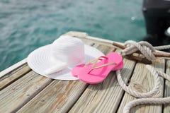 Chiuda su del cappello, della protezione solare e delle pantofole alla spiaggia Immagine Stock