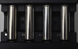 Chiuda su del caricabatteria con le batterie ricaricabili Fotografie Stock