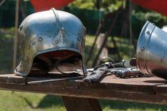 Chiuda su del casco d'argento medievale sulla Tabella di legno con l'indumento del ` s del cavaliere immagine stock libera da diritti