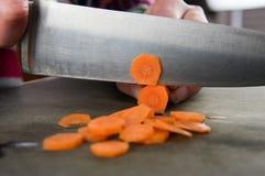 Chiuda su del coltello che affetta le carote immagini stock libere da diritti
