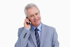 Chiuda su del commerciante maturo sorridente sul suo telefono cellulare Fotografia Stock
