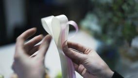 Chiuda su del commesso del fiore che fa una decorazione del nastro video d archivio