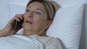Chiuda su del contagoccia, paziente femminile turbato che si trova a letto telefono di conversazione, cattive notizie stock footage