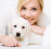 Chiuda su del cucciolo bianco che si trova sul sofà con la donna fotografia stock