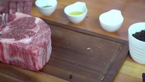 Chiuda su del cuoco unico o del cuoco gastronomico che condisce il bello pezzo fresco del pezzo della ghiottoneria di manzo con s archivi video