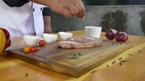 Chiuda su del cuoco unico o del cuoco gastronomico che condisce il bello pezzo fresco del pezzo della ghiottoneria di manzo con s video d archivio