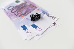 Chiuda su del denaro contante nero dell'euro e dei dadi Immagini Stock