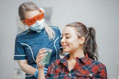 Chiuda su del dentista della donna che dà la tazza di plastica con acqua ad un cliente fotografie stock