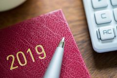 Chiuda su del diario 2019 con lo scrittorio di Pen And Calculator On Wooden immagini stock