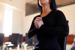 Chiuda su del dio pregante della donna triste in chiesa fotografie stock libere da diritti