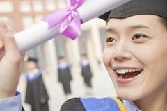 Chiuda su del diploma sorridente della giovane femmina e di tenuta laureato Fotografia Stock