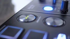Chiuda su del dito che preme il tasto di riproduzione dello strumento del DJ stock footage