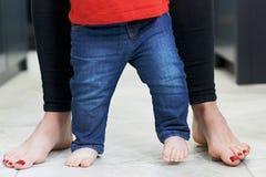 Chiuda su del figlio d'aiuto del bambino della madre per camminare in cucina fotografia stock
