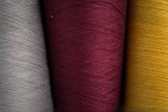 Chiuda su del filato cucirino grigio, marrone rossiccio e giallo Fotografia Stock Libera da Diritti