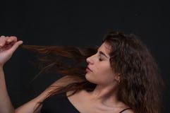 Chiuda su del fronte castana della ragazza attraente che gioca con i suoi capelli marroni ondulati lunghi fotografie stock