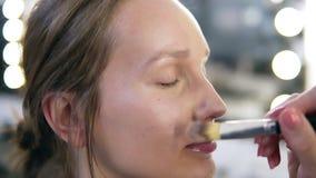 Chiuda su del fronte della giovane donna che ottiene la base sul suo fronte con una spazzola Sta sorridendo Componga lo studio stock footage