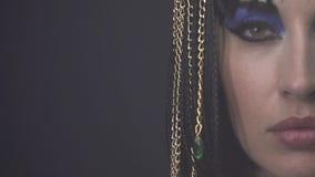 Chiuda su del fronte di Cleopatra con le catene blu dell'oro e di trucco in suoi capelli stock footage