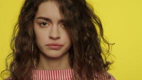 Chiuda su del fronte triste della ragazza Donna offensiva che guarda alla macchina fotografica su fondo giallo stock footage
