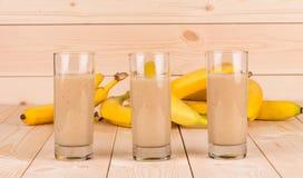 Chiuda su del frullato e dei frutti della banana su legno Immagine Stock