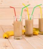 Chiuda su del frullato e dei frutti della banana su legno Fotografie Stock Libere da Diritti